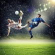 Two football players striking the ball — Stock Photo #21114063