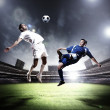 Two football players striking the ball — Stock Photo #21114177