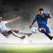 Two football players striking the ball — Stock Photo #21114189