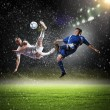 Two football players striking the ball — Stock Photo #21114261