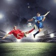 Two football players striking the ball — Stock Photo #21114299
