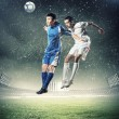 Two football players striking the ball — Stock Photo #21114331