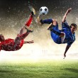 Two football players striking the ball - Stock Photo