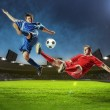 Two football players striking the ball — Stock Photo #21114611