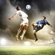 Photo: Two football players striking ball