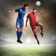 Two football players striking the ball — Stock Photo #21114915