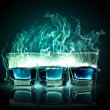 Three glasses of burning emerald absinthe - Stock Photo