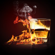 Glass of burning yellow absinthe - Stock Photo