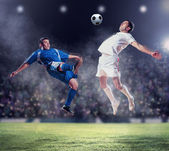 Two football players striking the ball — Foto de Stock