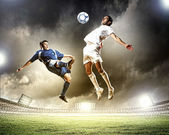 Two football players striking the ball — Stok fotoğraf