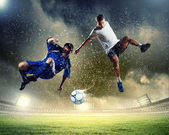 Two football players striking the ball — Stock Photo