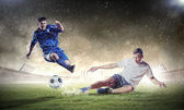 Two football players striking the ball — Stockfoto