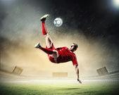 поражает мячом игрок футбола — Стоковое фото