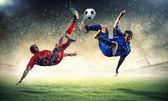 Dos jugadores de fútbol golpeando la pelota — Foto de Stock
