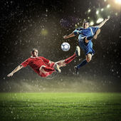 Two football players striking the ball — 图库照片