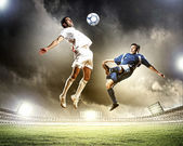 Two football players striking the ball — ストック写真
