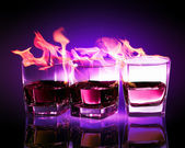 Three glasses of burning purple absinthe — Stock Photo