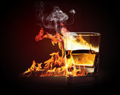 Glass of burning yellow absinthe — Stock Photo