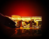 Three glasses of whiskey with ice cubes — Stock Photo