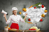 Asian female cook holding megaphone — Stock Photo