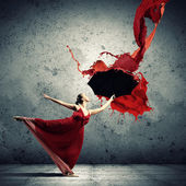 Ballet dancer in flying satin dress with umbrella — Stock Photo