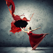 Ballet dancer in flying satin dress with umbrella — Stockfoto