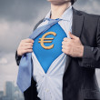 Businessman showing superman suit underneath shirt - Stock Photo