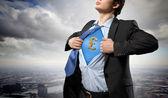 Businessman showing superman suit underneath shirt — Stock Photo