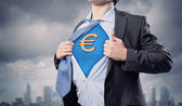 Businessman showing superman suit underneath shirt — Stockfoto