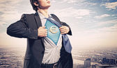 Businessman showing superman suit underneath shirt — Photo