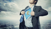 Businessman showing superman suit underneath shirt — Stock fotografie