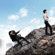 Two businessmen pulling rope atop of mountain — Stock Photo
