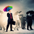 Businessman with umbrella - Stock Photo