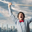 Businessman hanging on rope - Stock Photo