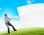 Adult man pulling blank banner — Stock Photo