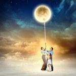 Family pulling moon — Stock Photo