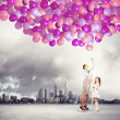 Family holding colorful balloons — Stock Photo #26355723