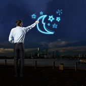 Businessman draws a moon and stars — Photo