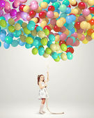 Little girl holding balloons — Stock Photo