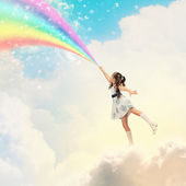 Little girl drawing rainbow — Stock Photo