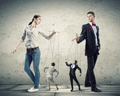 Businesspeople with marionettes — Stock Photo