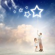 Family pulling rope with a star symbol — Stock Photo #29195895