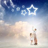 Aile bir yıldız sembolü iple çekiyor — Stok fotoğraf