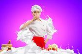 Asian female cook against milk splashes — Stock Photo