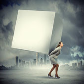 Businesswoman carrying cube — Stockfoto