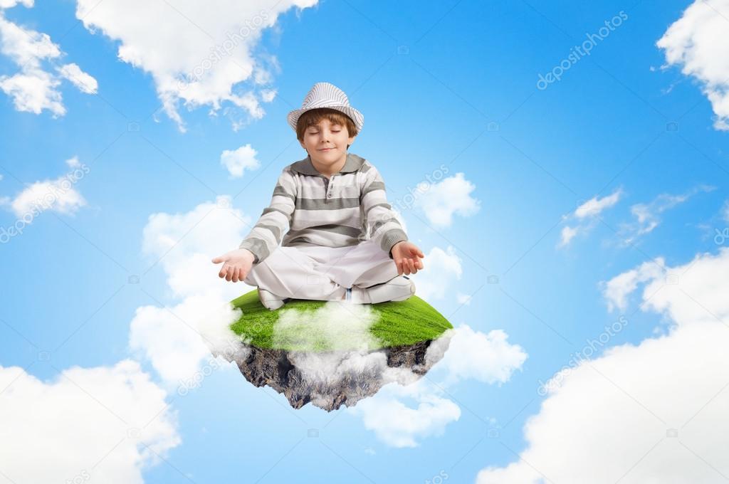 小男孩坐在云上和放松的形象