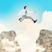 Businessman jumping over gap — Stock Photo