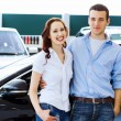 Young happy couple at car salon — Stock Photo