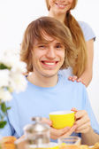 Young happy man drinking tea — Stock Photo