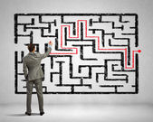 Businessman solving labyrinth problem — Stockfoto